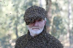 George McGavin covered in bees.